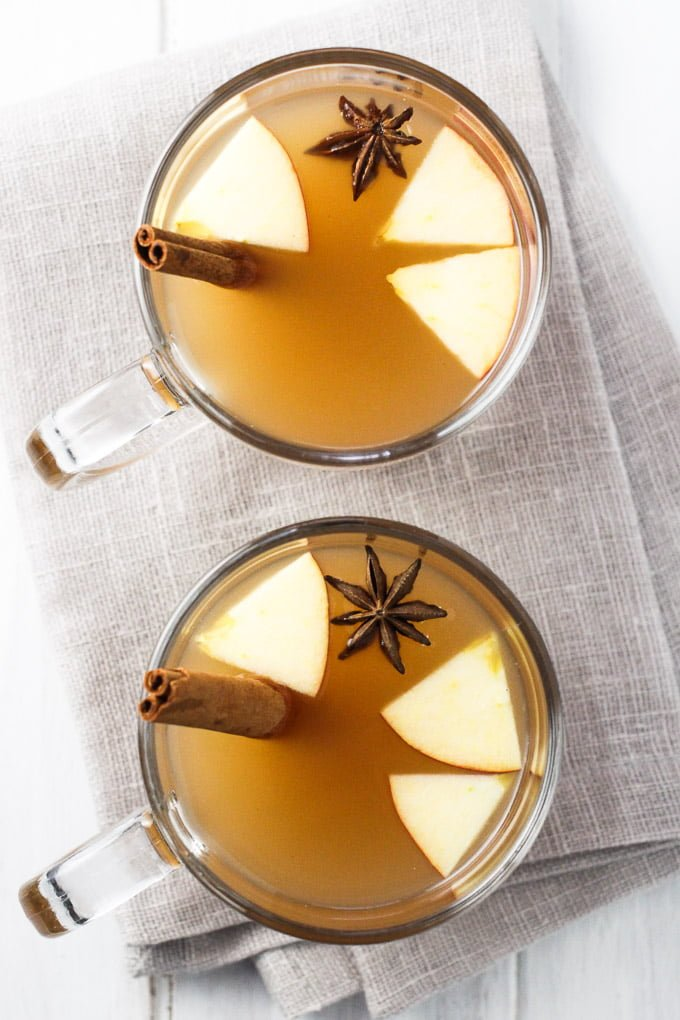 Hot apple cider in glasses. Garnished with star anise, apple slices, and cinnamon sticks. Top view.