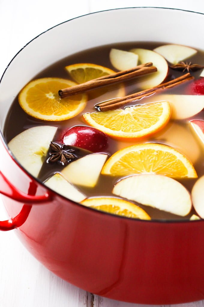 Hot apple cider in a pot. Garnished with orange and apple slices and cinnamon sticks.