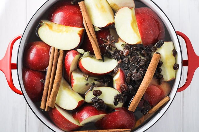 Sliced apples, raisins, cinnamon sticks, star anise, and water in a pot. Top view.