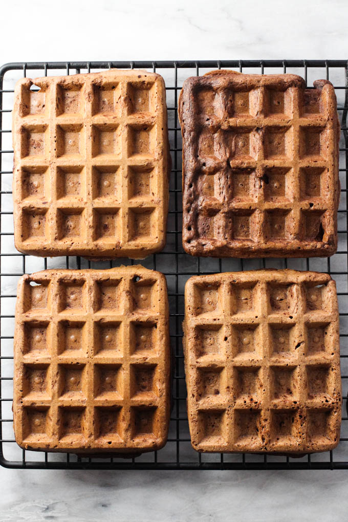 Four healthy chocolate waffles on a cooling rack. Top view.