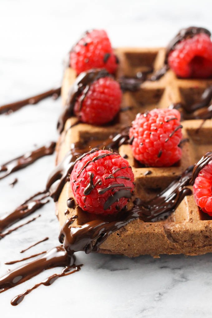 Chocolate waffle topped with fresh raspberries and chocolate sauce. Side view.