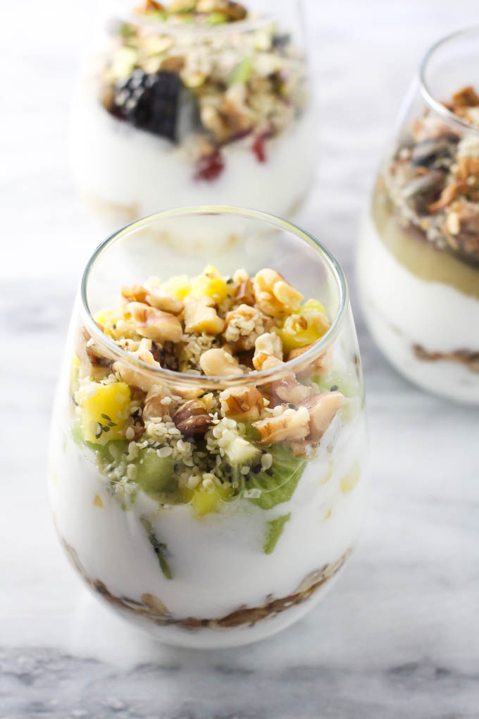 Fruit and nut yogurt parfait in a glass on a marble back ground.