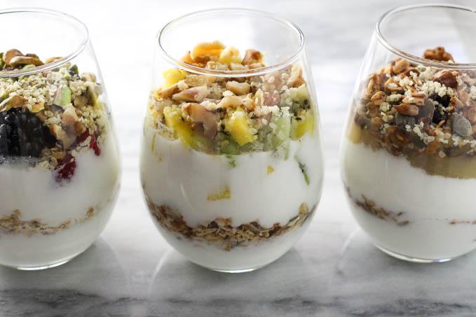Three yogurt parfaits in wine glasses on marble background.