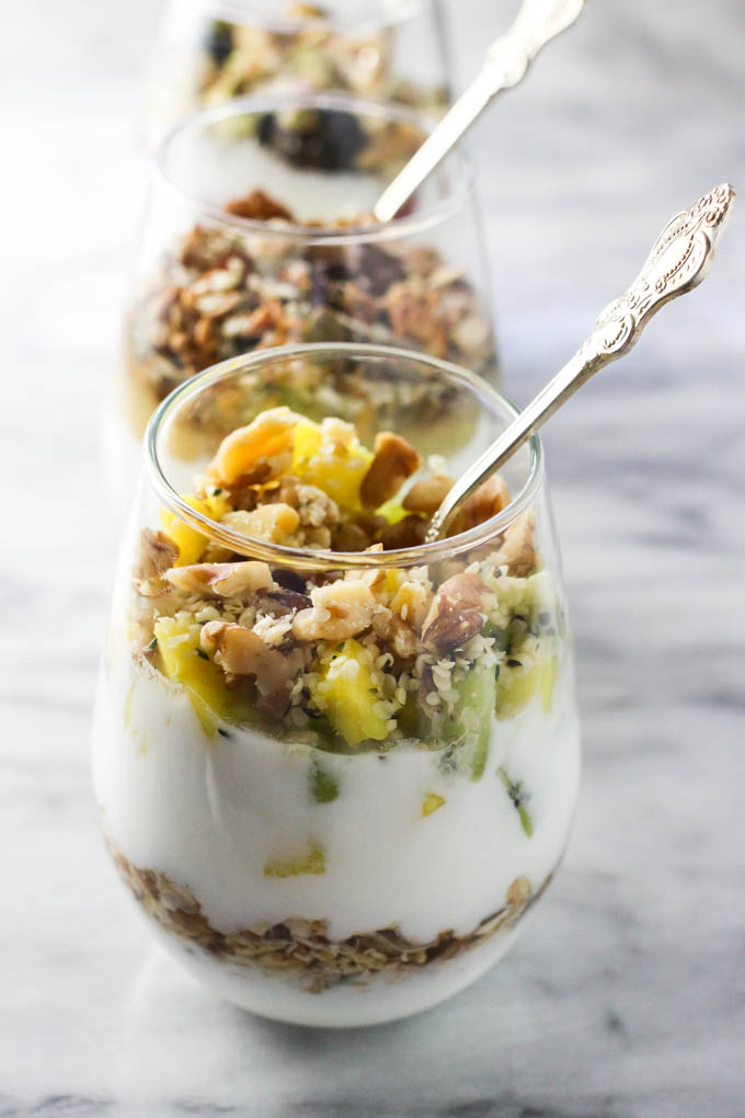 Yogurt parfait in glasses on marble background.