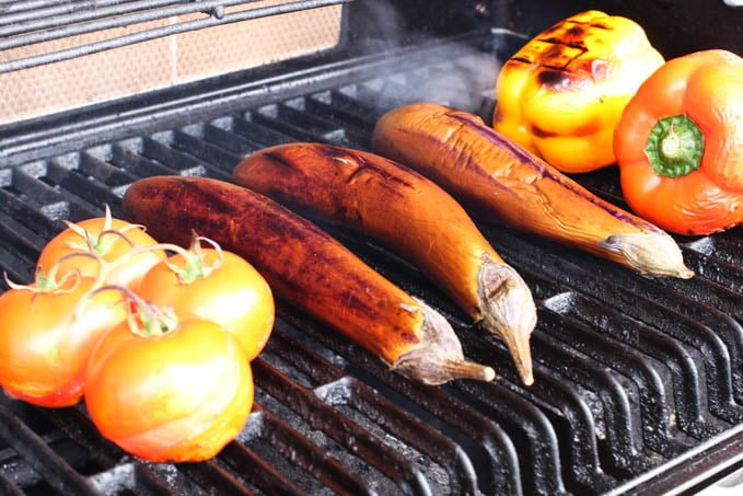 Tomatoes, Chinese eggplants, and bell peppers on an outdoor grill.