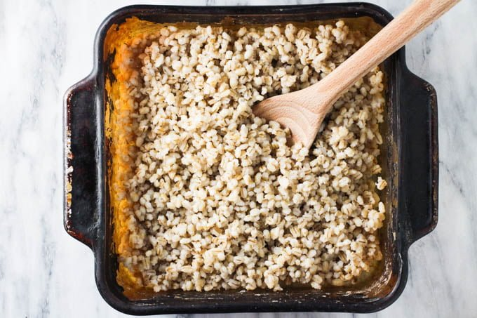 Oven-baked pot barley in a baking dish with a wooden spoon.