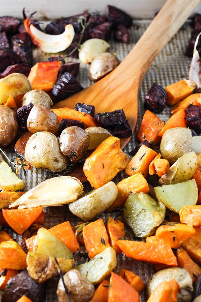 Roasted root vegetables on a baking sheet with a wooden spatula.