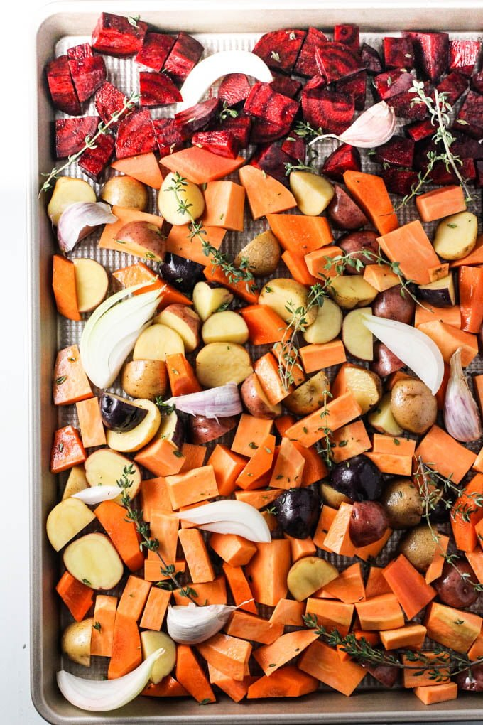 Raw chopped root vegetables on a baking sheet.