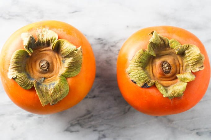 Two Fuyu persimmons on marble background.