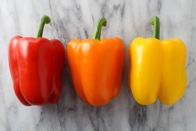 Three fresh bell peppers - red, orange, and yellow.