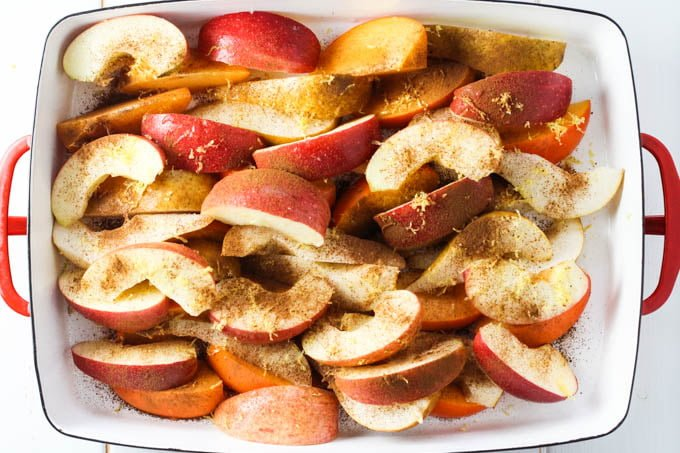 Fruit slices in a baking dish sprinkled with lemon zest and cinnamon.