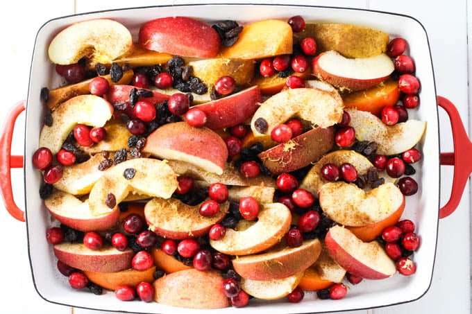 Fruit slices, cranberries, and raisins in a baking dish.