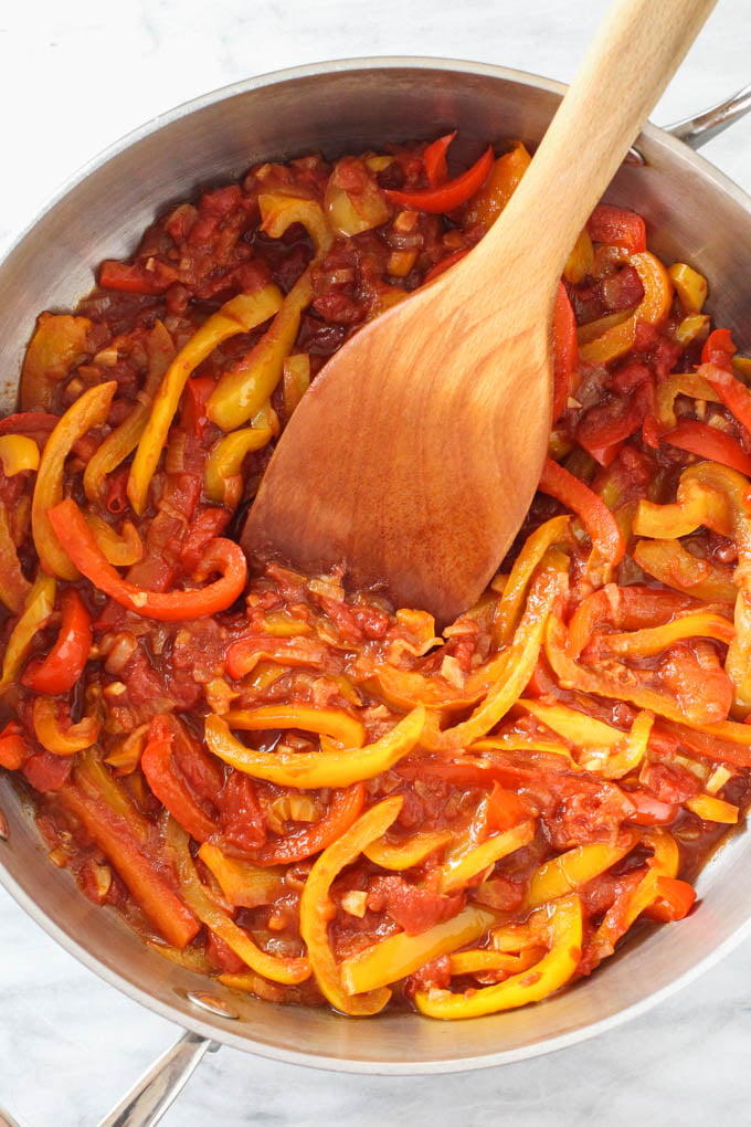 Peperonata in a skillet with a wooden spatula in it.