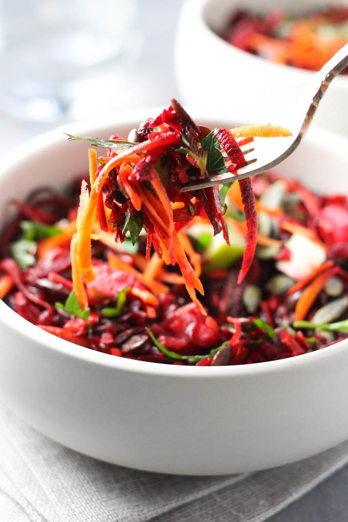 Beet and carrot pieces on a fork.
