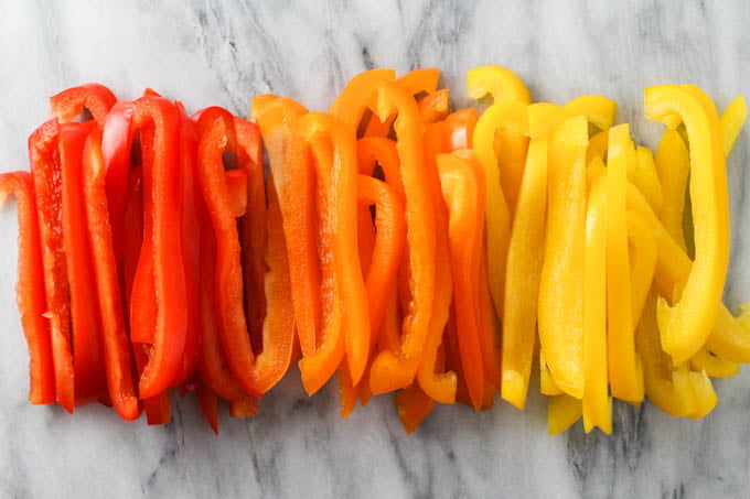 Red, orange, and yellow bell peppers sliced into thin strips.