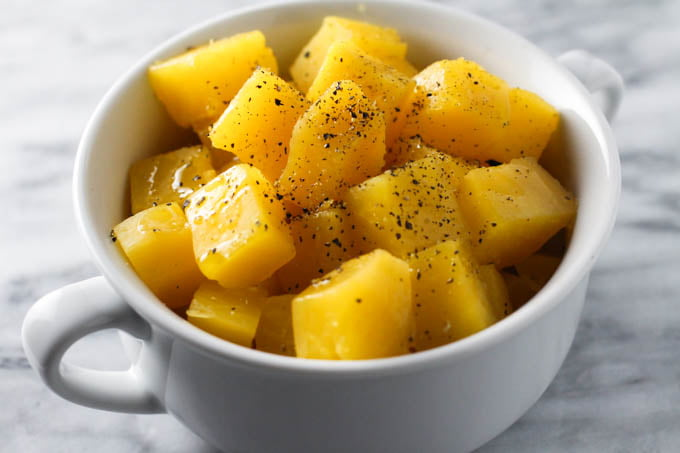 Boiled rutabaga in a white dish. Seasoned with ground black pepper.