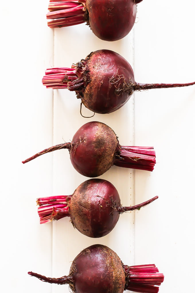 Red beets on a white board.