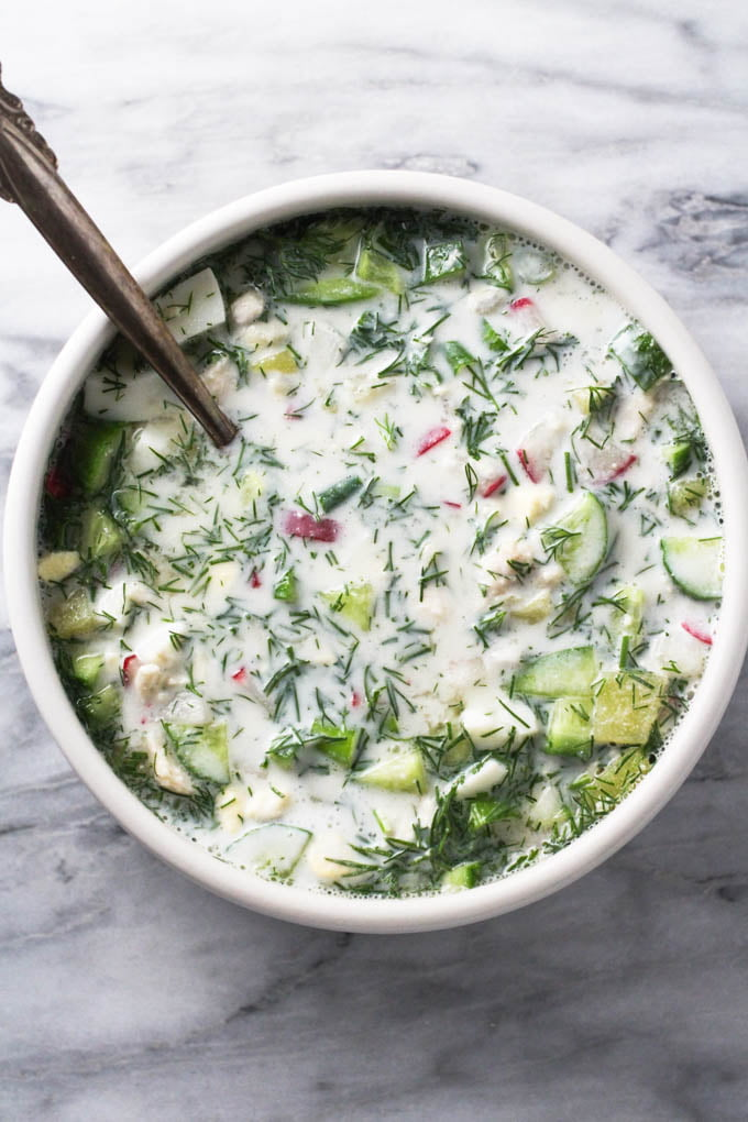 Top view of okroshka soup in a bowl on marble background.