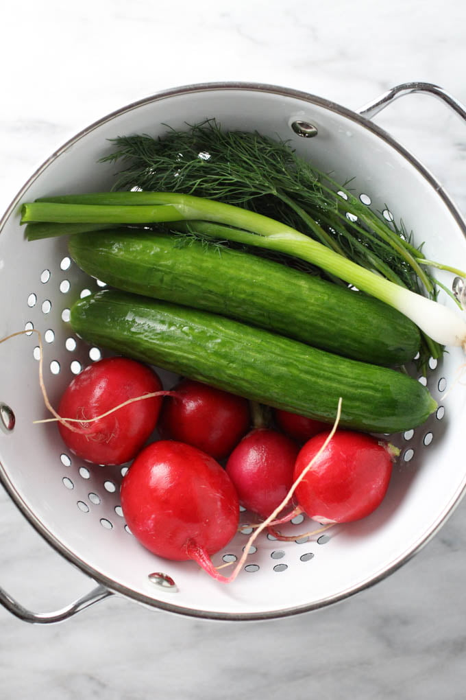 Washed radishes, cucumbers, green onions, and dill in a colander.