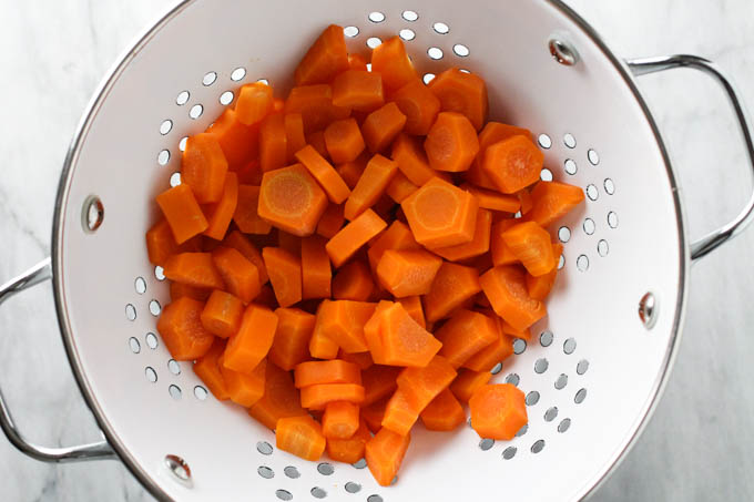 Parboiled carrots inside a colander.