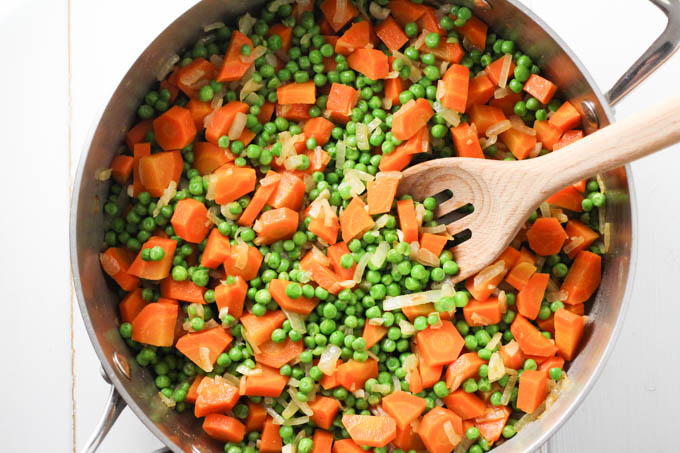 Top view of peas and carrots in a pan.