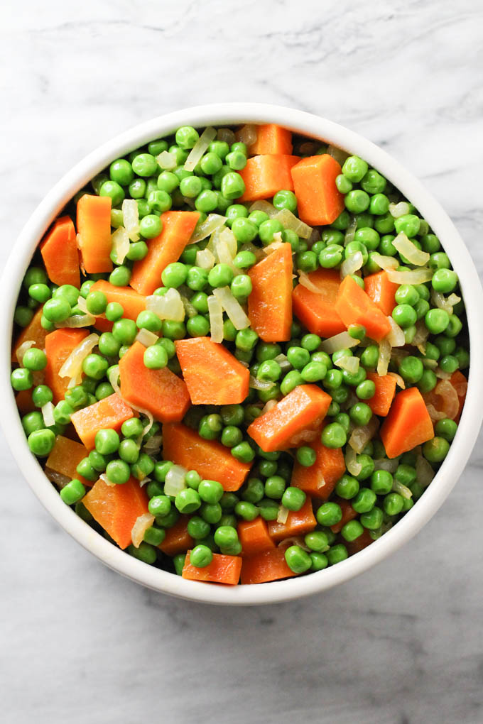 Peas and carrots in a bowl. Top view.