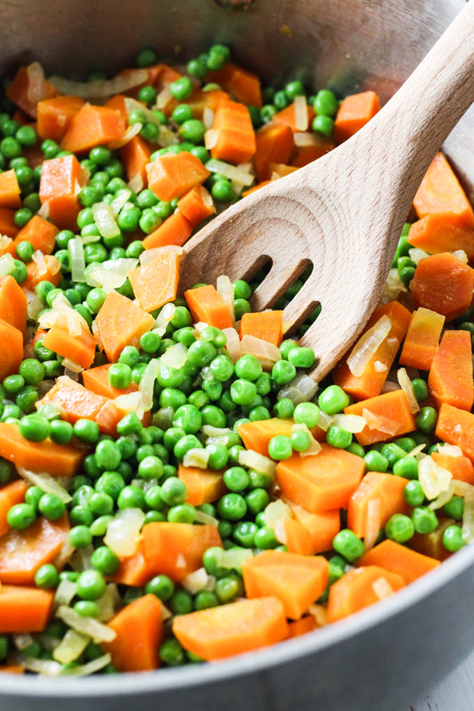 Close up of peas and carrots in a pan.