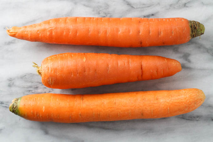 Three raw unpeeled carrots on a marble background.