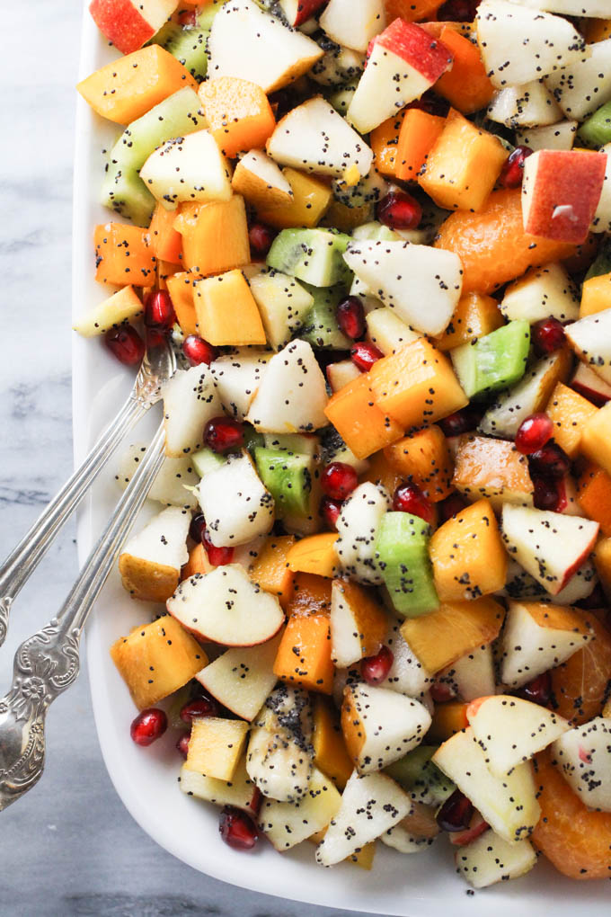Fall and winter fruit salad on a platter standing on a marble background.