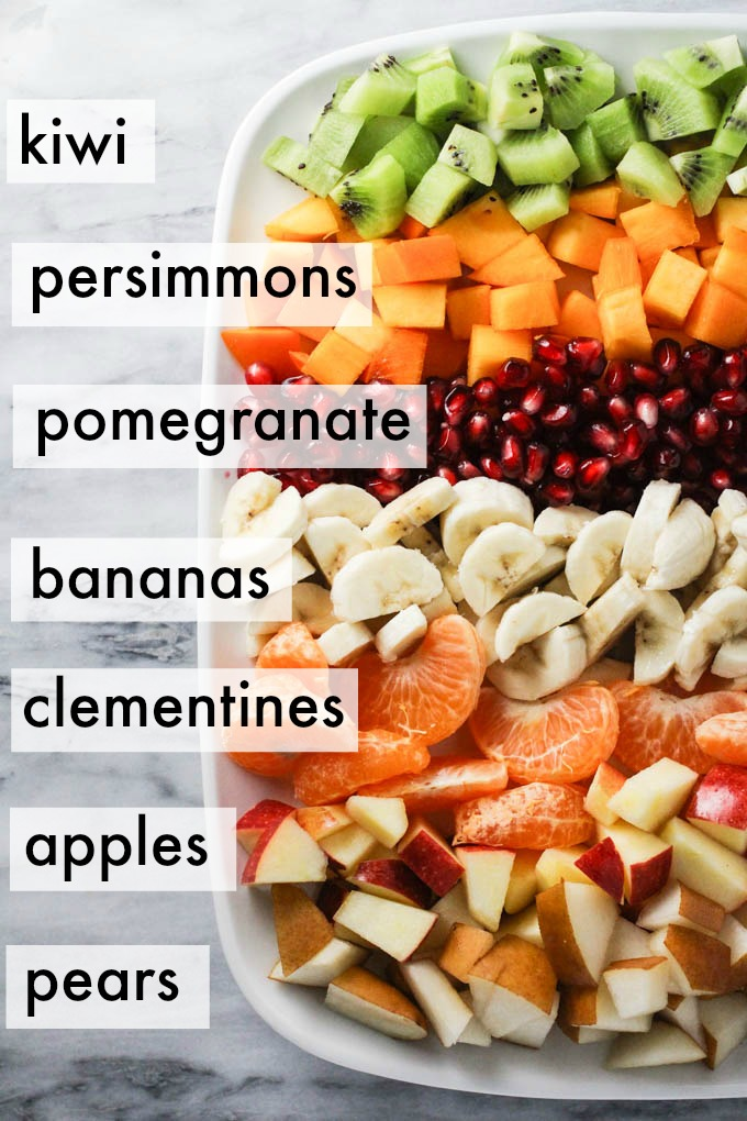 Ingredients for the winter fruit salad displayed in rows on a platter.