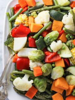 Instant Pot steamed vegetables on a white platter.