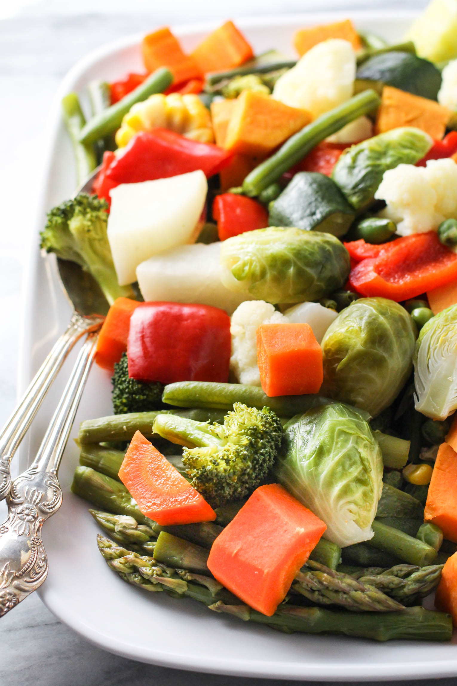 Steamed vegetables on a white platter.