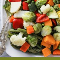 Instant Pot steamed vegetables on a white platter with silver serving spoons to the left. Under the image, there are words: Instant Pot Steamed Vegetables.