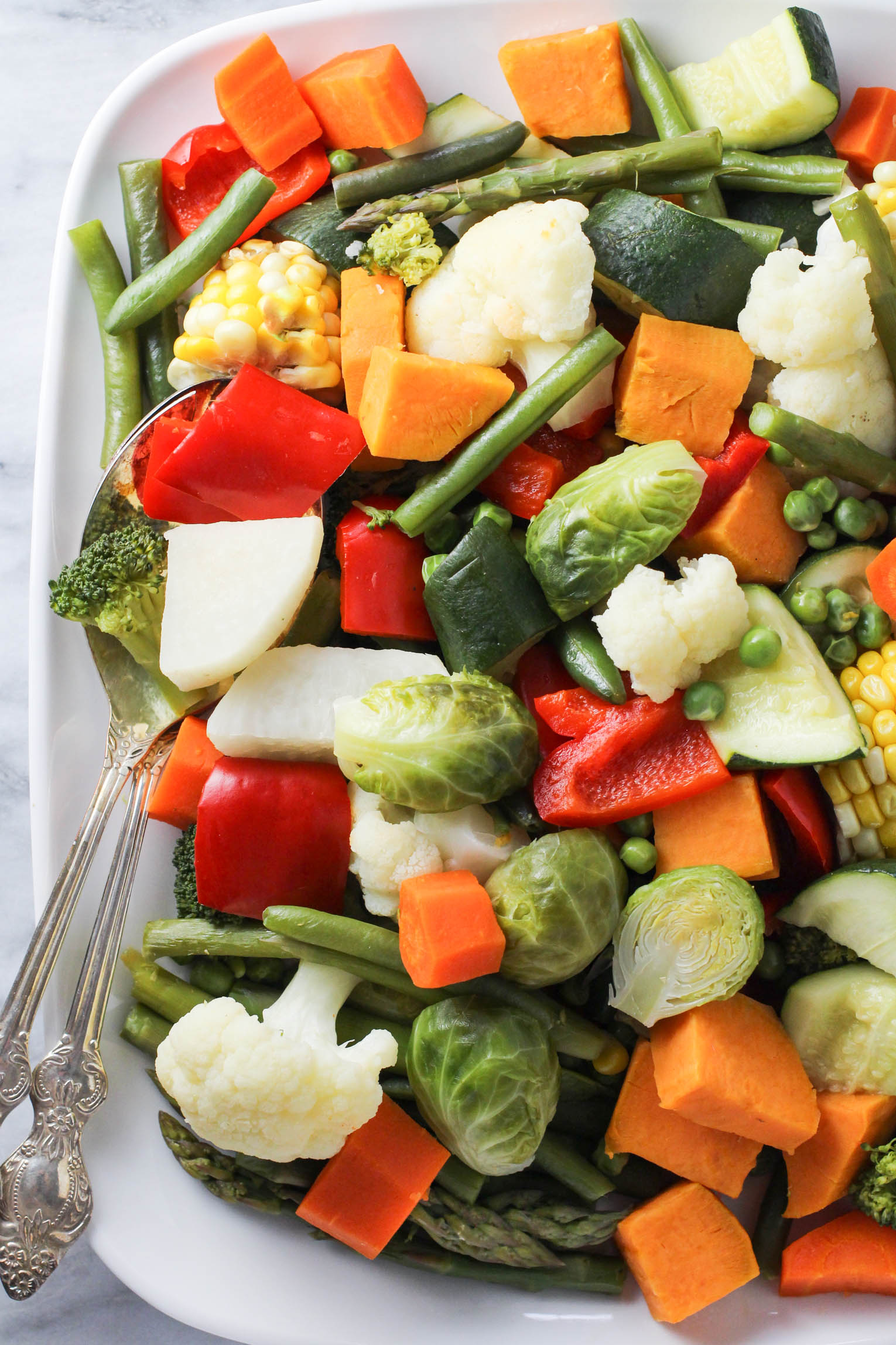 Instant Pot steamed vegetables on a white platter. Two silver serving spoons on the left side.